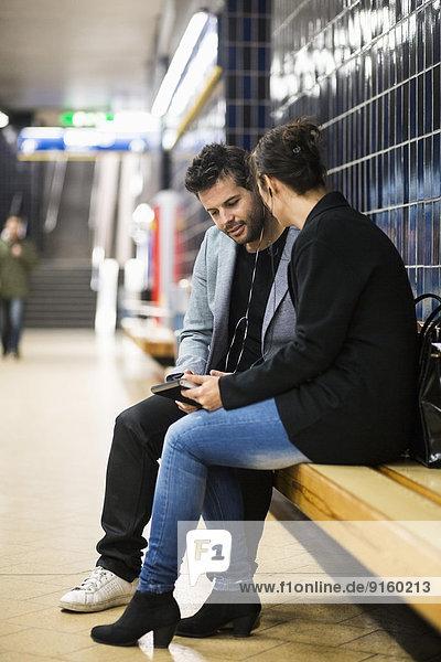 Volle Länge der Geschäftsleute  die sich an der U-Bahnstation unterhalten