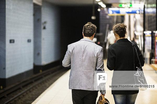 Rückansicht der an der U-Bahnstation wartenden Geschäftsleute