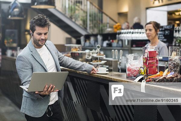 Mittlerer Erwachsener Mann mit Laptop beim Kaffeekauf im Cafe