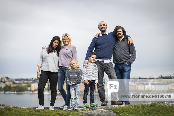 Full length portrait of homosexual families standing together at lakeshore