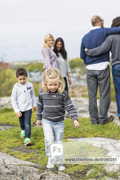 Kinder auf dem Felsen mit homosexuellem Paar im Hintergrund