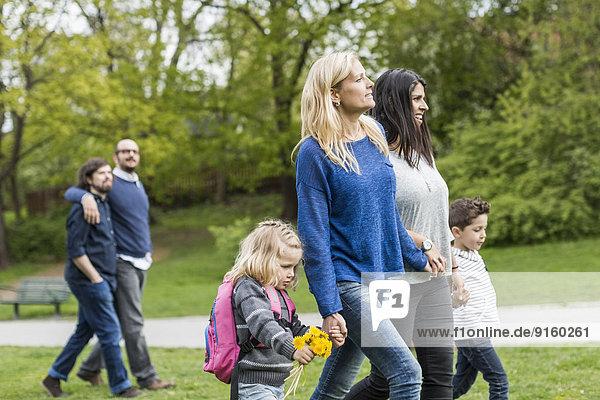 Weibliche homosexuelle Familie beim Spaziergang im Park mit schwulem Paar im Hintergrund