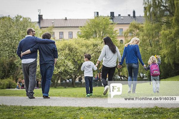 Rückansicht der weiblichen homosexuellen Familie beim Spaziergang im Park mit schwulem Paar im Hintergrund