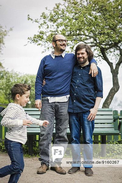 Zärtliches schwules Paar mit Sohn beim Spielen im Park
