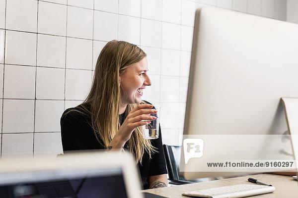 Lächelnde junge Geschäftsfrau bei einem Glas Wasser im neuen Büro