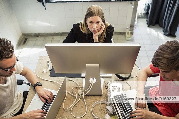 Hoher Blickwinkel auf junge Geschäftsleute  die Technologien im Kreativbüro einsetzen