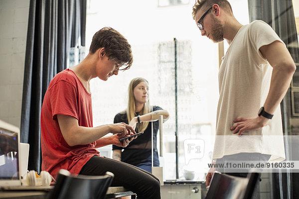 Junge Geschäftsleute mit digitalem Tablett und Kollegin im Hintergrund im neuen Büro