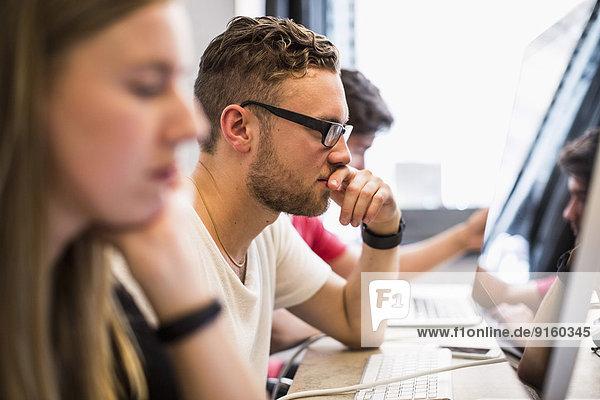 Seitenansicht eines jungen Geschäftsmannes mit Kollegen im neuen Büro