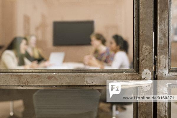 Blick auf Geschäftsfrauen im Vorstandszimmer durch Glastür im Kreativbüro