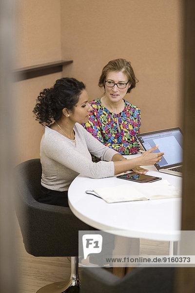 Geschäftsfrau im Gespräch mit Kollegin im Vorstandszimmer des Kreativbüros