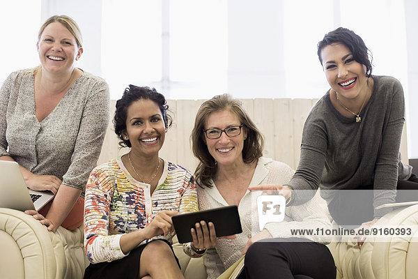 Portrait of happy businesswomen on sofa in creative office