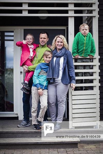 Porträt einer glücklichen Familie auf der Veranda