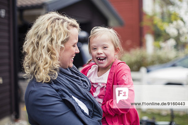 Portrait of girl with mother laughing in yard