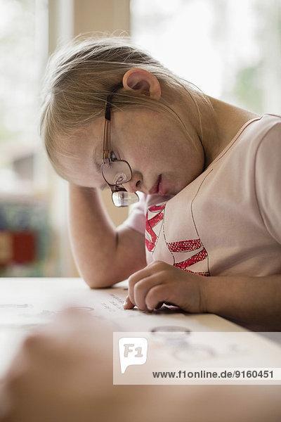 Mädchen mit Down-Syndrom beim Lernen am Tisch