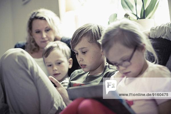 Geschwister sitzend mit Mutter im Haus