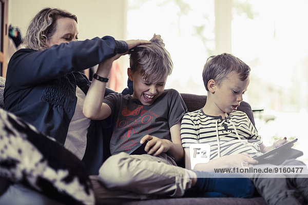 Playful mother pulling son's hair besides boy using digital tablet at home