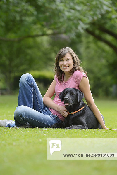Woman with a black labrador on a meadow  Bavaria  Germany  Europe