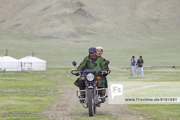 Ehepaar im traditionellen Deel fährt auf einem Motorrad  Terkhiyn Tsagaan Nuur  Nordsteppe  Archangai-Aimag  Mongolei