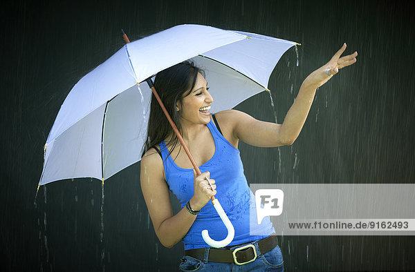 Lächelnde junge Frau mit Schirm genießt den Regen