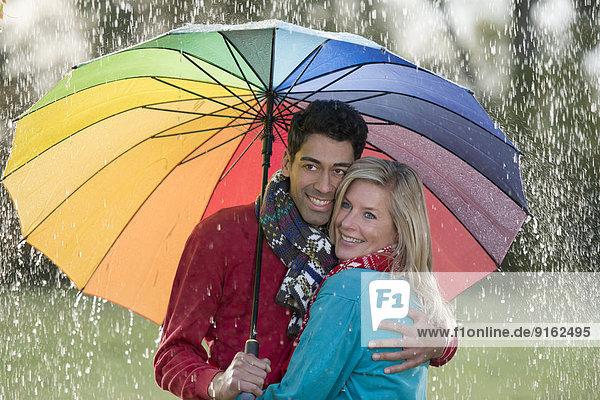 Lächelndes Paar unter regenbogenfarbenem Schirm genießt den Regen