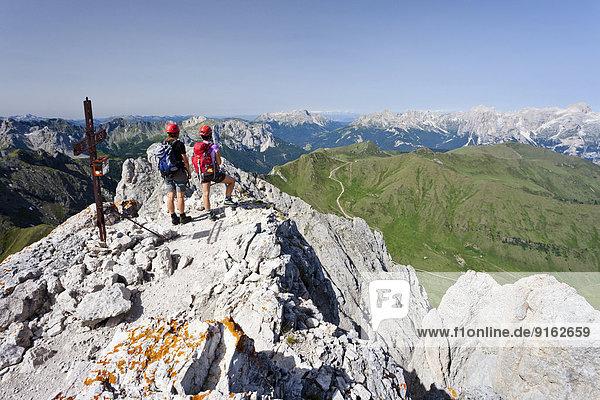Bergsteiger auf dem Gipfel des Colàc über den Klettersteig Via ferrata dei Finanzieri im Fassatal  Dolomiten  hinten die Rosengartengruppe und der Latemar  Trentino  Italien