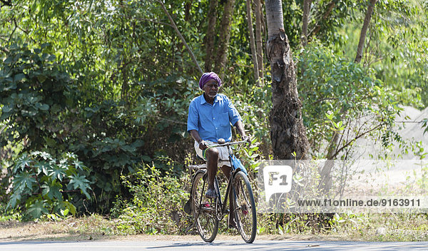 Mann fährt Fahrrad  Tamil Nadu  Indien