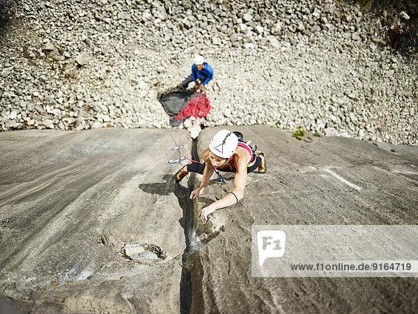 Woman lead climbing a gully  crack in the rock  Martinswand climbing area  Zirl  Tyrol  Austria