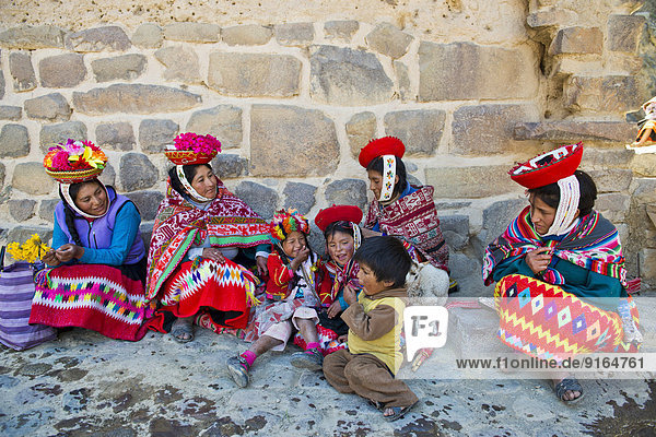 Women and children in traditional dress of the Quechua Indians sitting on the floor in front of a wall  Ollantaytambo  Urubamba Valley  Peru