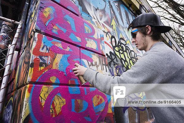Caucasian boy spraying graffiti on urban wall