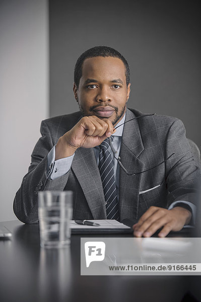 Mixed race businessman sitting in meeting