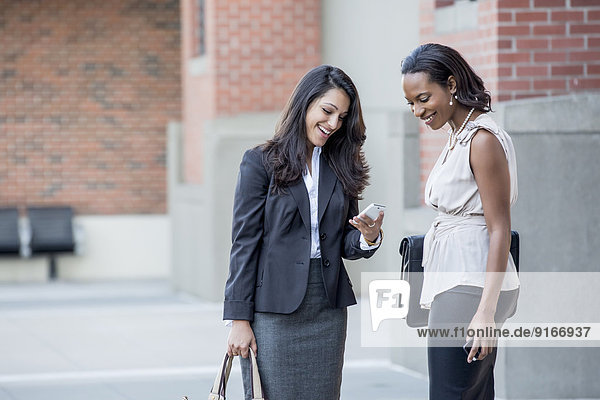 Businesswomen talking on city sidewalk