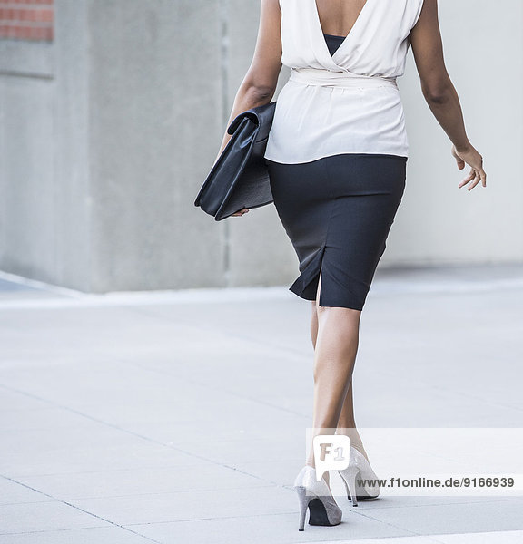 Black businesswoman walking on city street