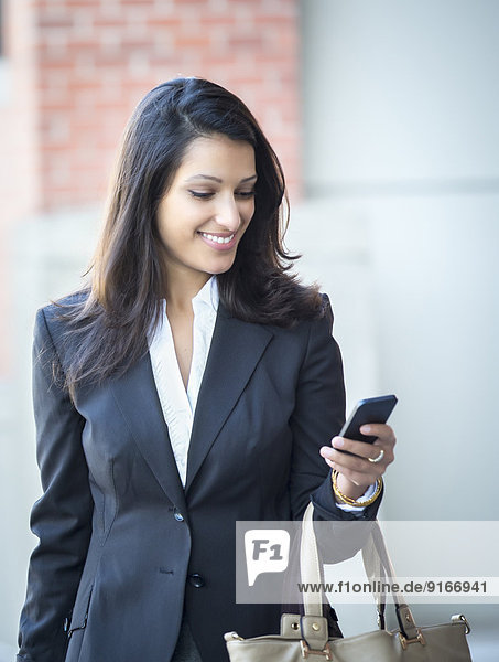 Mixed race businesswoman using cell phone on city street
