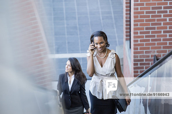 Black businesswoman talking on cell phone on escalator