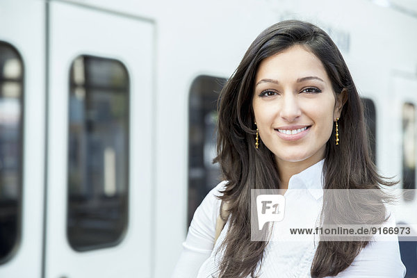 Mixed race businesswoman smiling on train platform