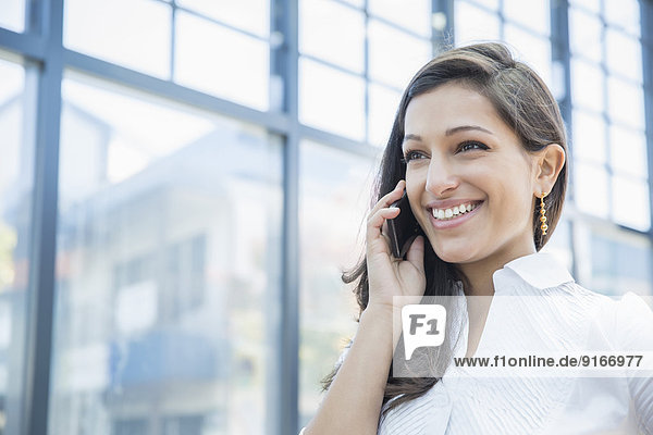 Mixed race businesswoman talking on cell phone outdoors