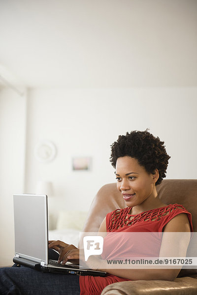 Black woman using laptop in armchair