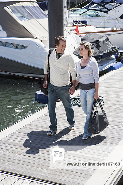 Caucasian couple walking on dock