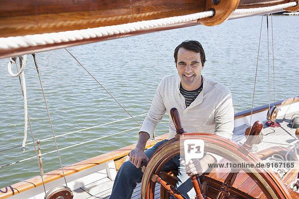 Caucasian man steering sailboat