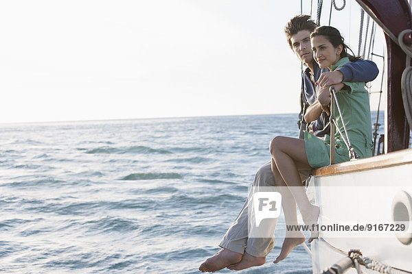 Caucasian couple relaxing on sailboat Caucasian couple relaxing on sailboat