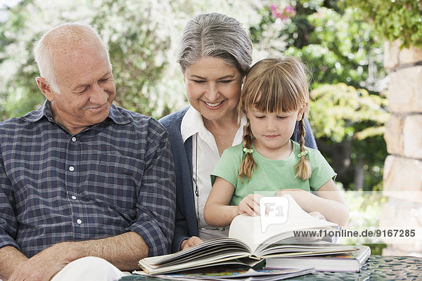 Grandparents and granddaughter reading outdoors
