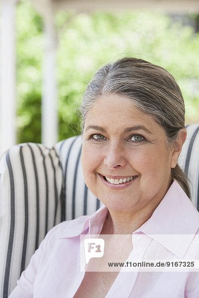Senior Caucasian woman smiling on porch