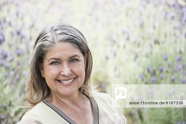 Caucasian woman smiling in lavender field