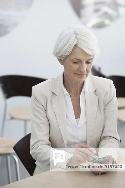 Senior Caucasian businesswoman using cell phone in cafe