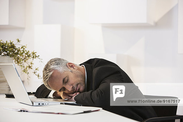 Businessman sleeping at desk in office