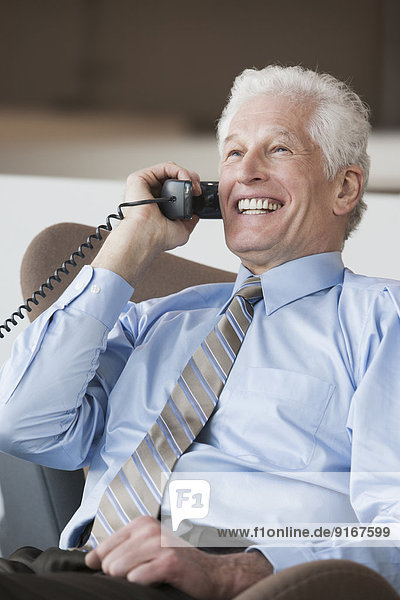 Caucasian businessman talking on telephone