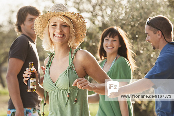 Woman drinking beer outdoors