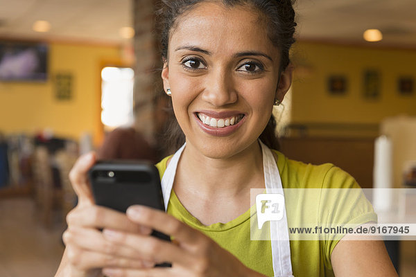 Hispanic server using cell phone in cafe