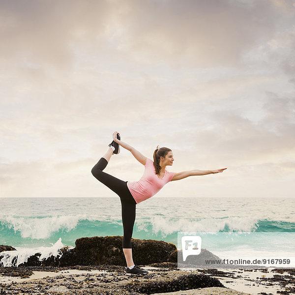 Caucasian woman stretching on beach