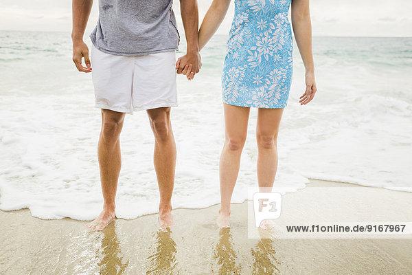Caucasian couple holding hands on beach